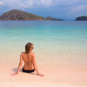 Young sexy woman in bikini enjoying the sun on the beach — Stock Photo