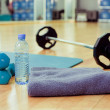 Bottle of water, sports towel and exercise equipment — Stock Photo #24494267