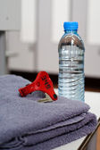 Bottle of water and towel in locker room — Stock Photo