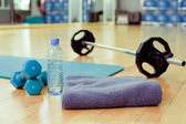 Bottle of water, sports towel and exercise equipment — Stock Photo