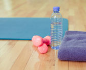 Bottle of water, sports towel and exercise equipment — Стоковое фото