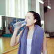 Young  woman drinking water, at fitness club or gym — Stock Photo