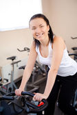 Beautiful woman on an exercise bike at the gym — Stock Photo
