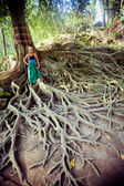 Young woman standing on the tree roots — Stockfoto