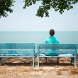 Young man sitting on bench facing the sea — Stock Photo