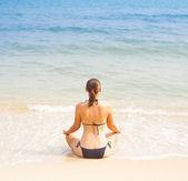 Caucasian woman practicing yoga on beach — Stock Photo