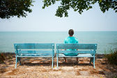 Young man sitting on bench facing the sea — Stock fotografie