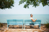 Young woman sitting on bench facing the sea — Stock Photo