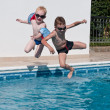 Royalty-Free Stock Photo: Two boys jumping into swimming pool