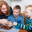 Family decorating gingerbread house — Stock Photo