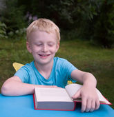 6-year old boy reading book and smiling — Stock Photo