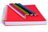Oranžové poznámkového bloku a barevné tužky — Stock fotografie