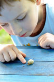 Boy touching snail — Stock Photo