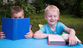 8-year and 6-year old boys reading books and smiling — Stock Photo