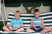 8-year schoolboy and 6-year preschooler reading books — Stock Photo