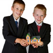 Two boys holding toy house — Stock Photo