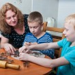 Family making gingerbread cookies - Stock Photo