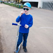 Royalty-Free Stock Photo: Cute boy wearing sunglasses riding scooter