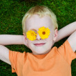 Royalty-Free Stock Photo: Young boy with daisies on eyes