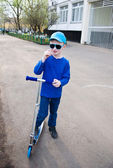 Cute boy wearing sunglasses riding scooter — Stock Photo