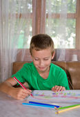 Young boy drawing and smiling — Stock Photo