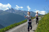 Two brothers running on mountain path — Stock Photo