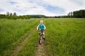 Nice boy cycling in the field — Stock Photo
