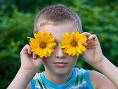 Cute boy with flowers on eyes having fun — Stock Photo
