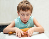 Young boy rolling gingerbread dough — Stock Photo