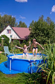 Two boys jumping and splashing in swimming pool — Stock Photo