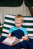6-year old boy reading book outdoors — Stock Photo