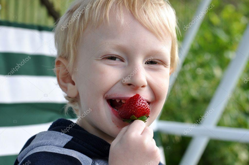 可爱的金发小男孩吃草莓– 图库图片