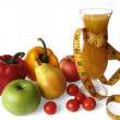 Fruits and vegetables and a glass of juice wrapped with measure - Stock Photo