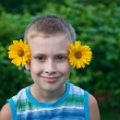 Cute boy with flowers on ears having fun — Stock Photo