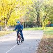 Stock Photo: Child riding bicycle in autumn park