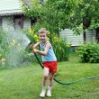 Boy watering lawn with hose — Stock Photo