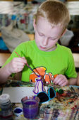 Boy painting russian toy — Stock Photo