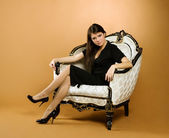 Young woman sitting in armchair — Stock Photo