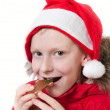 Smiling boy eating gingerbread man. — Stock Photo #16791143