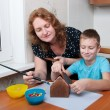 Mother and son making gingerbread house - Stock Photo