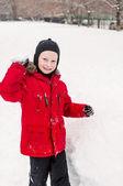 Garçon souriant, jetant des boules de neige — Photo