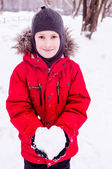 Leende pojke håller snön hjärta — Stockfoto