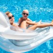Two boys having fun playing on a floating mattress in a swimming — Stock Photo