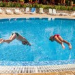 Stock Photo: Two boys diving into pool