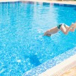 Stock Photo: Young boy jumping into swimming pool