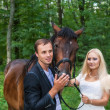 Bride and groom with a horse — Stock fotografie