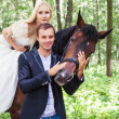 Newlywed couple standing next to a horse — Stock Photo