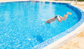 Young boy jumping into swimming pool — Stock Photo