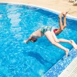 Stock Photo: Two boys jumping into swimming pool
