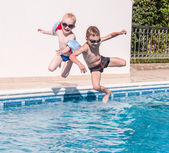 Two boys jumping into swimming pool — Stock Photo